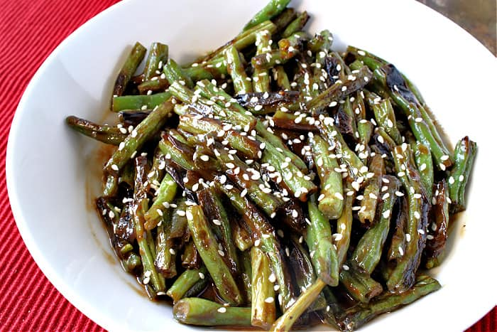 An offset photo of a bowl of blistered green beans with sesame seeds and miso sauce on a red background.