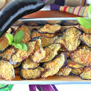 A small baking tray filled with crispy baked eggplant chips with an whole eggplant and fresh basil as garnish