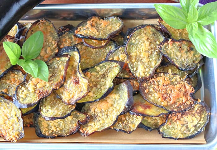 A direct overhead closeup photo of a  tray of eggplant snack chips with Parmesan cheese and fresh basil al garnish