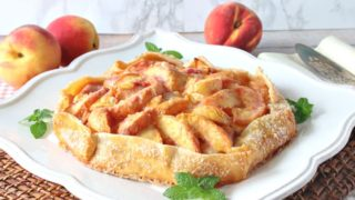 A fresh peach crostata on a square white platter with mint garnish and fresh peaches in the background.