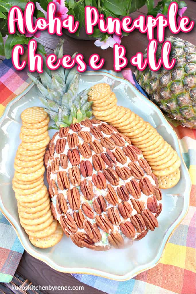 Overhead vertical photo of an aloha pineapple cheese ball with pecans and crackers on a serving platter with a title text overlay graphic