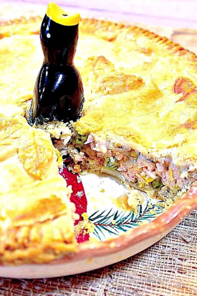 Closeup vertical photo of a pork pot pie with a slice taken out and a pie bird in the center.
