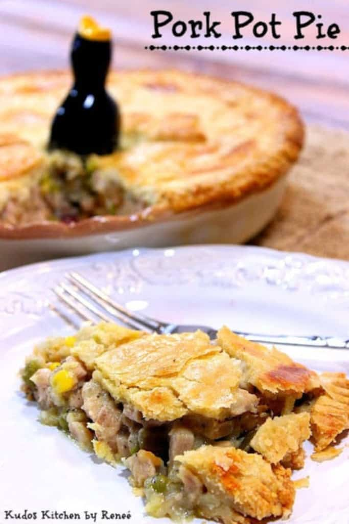 A vertical photo of a slice of pork pot pie in the foreground and the entire pie in the background.