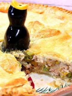A closeup horizontal photo of a pork pot pie with a slice taken out and a pie bird on top