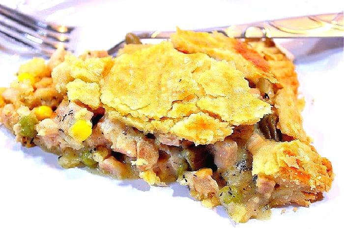 A closeup of a slice of pork pot pie on a plate the a fork.