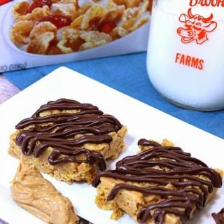 A vertical closeup photo of tiger paws cereal bars with a chocolate drizzle and a knife with peanut butter