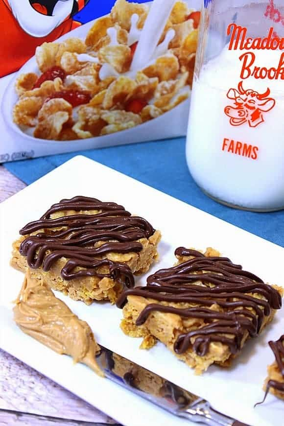 A vertical closeup image of tiger paws cereal bars on a white plate with a milk bottle and cereal box in the background.