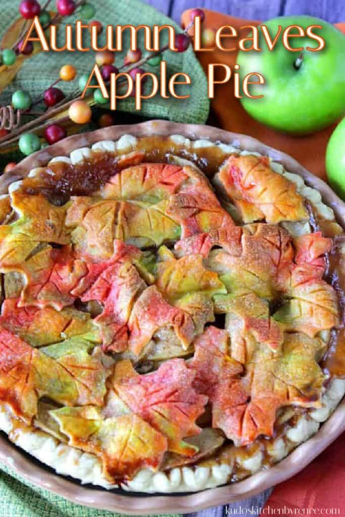 A vertical closeup photo of an apple pie with colorful autumn leaves crust and a title text overlay graphic