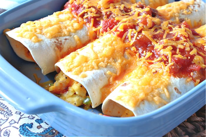 A closeup horizontal photo of three Air Fryer Breakfast Burritos with salsa and cheese in a blue dish