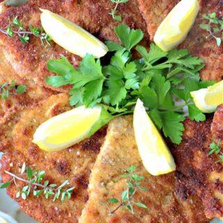 A vertical overhead closeup of German Pork Schnitzel on a platter with fresh herbs and lemon wedges