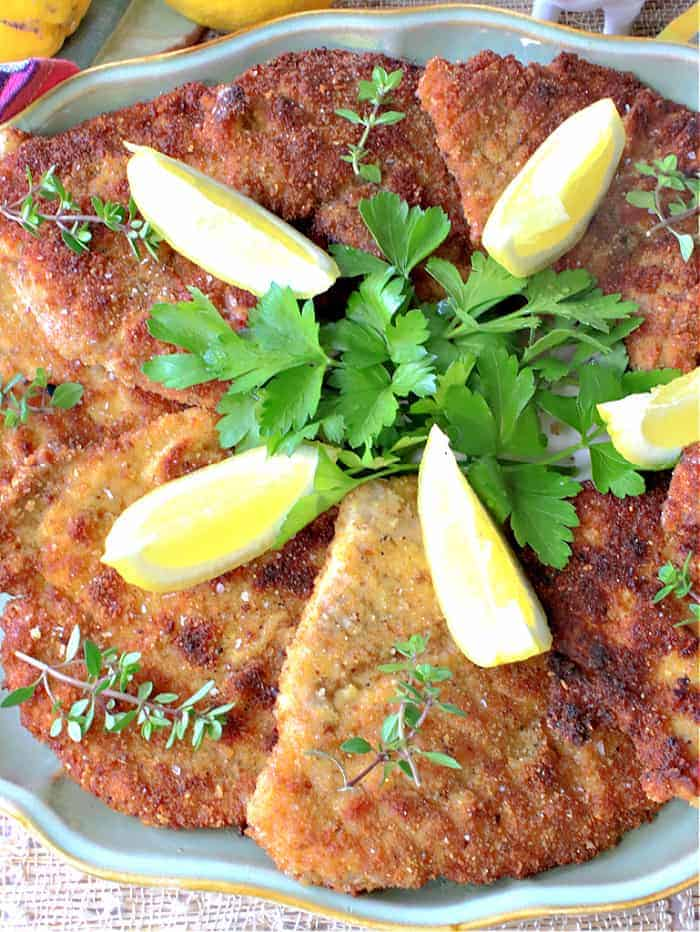An overhead closeup picture of German Pork Schnitzel on a platter with lemon wedges and fresh green herbs.