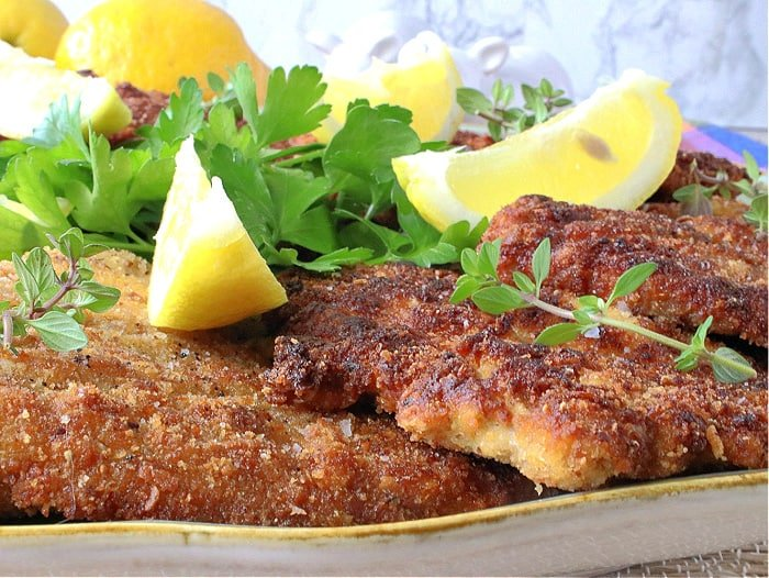 A closeup horizontal photo of a platter filled with golden brown German Pork Schnitzel along with fresh herbs and lemon wedges.