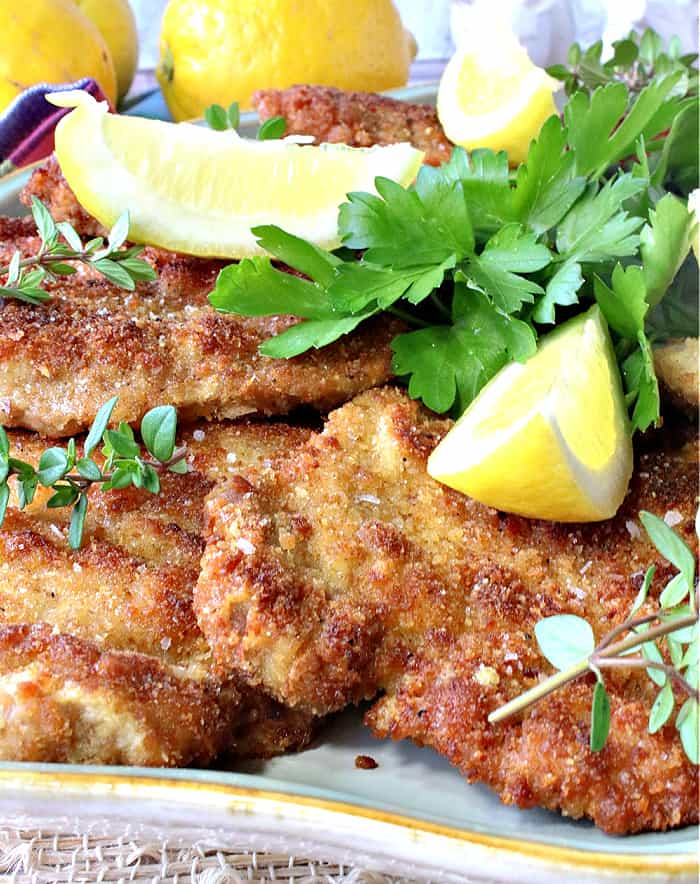 A closeup vertical picture of a golden brown German Pork Schnitzel with fresh herbs and lemon wedges.