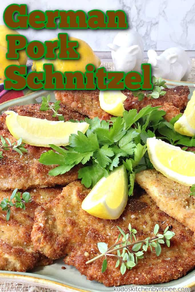 A vertical closeup photo fo German Pork Schnitzel on a plate with fresh herbs and lemons along with a title text overlay graphic