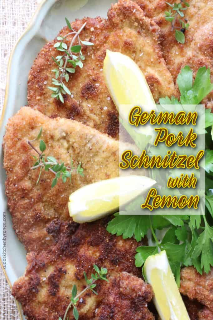 A closeup overhead vertical photo of German Pork Schnitzel with fresh herbs and lemon wedges along with a title text overlay graphic.