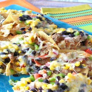 A colorful photo with loaded pulled pork nachos on a blue platter with a lime green and orange napkin in the background