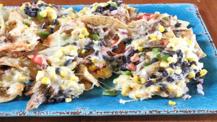 A blue platter filled with Loaded Pulled Pork Nachos with melted cheese, corn, and black beans
