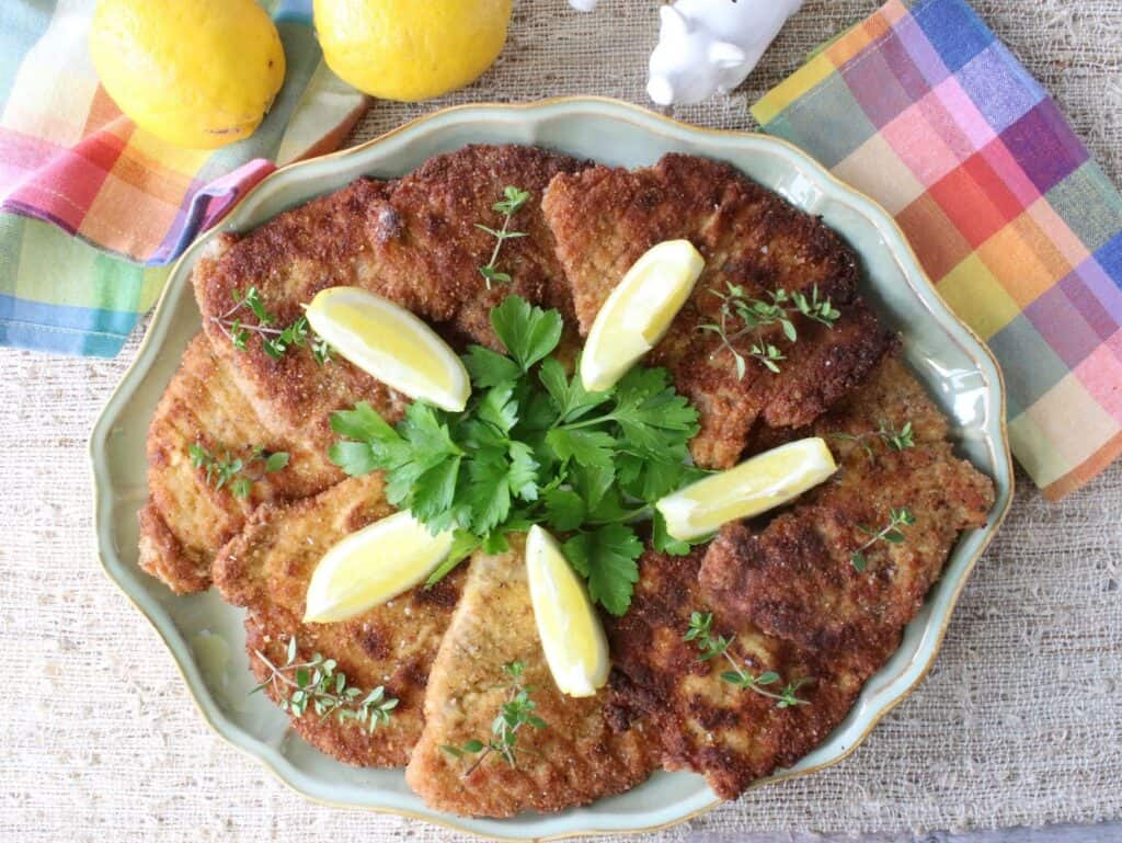 An overhead photo of a platter of German Pork Schnitzel with fresh herbs, colorful napkins, and lemon wedges.