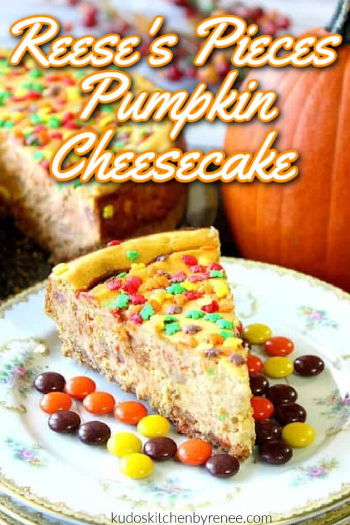 A closeup vertical image of a Reese's Pieces Pumpkin Cheesecake with fall sprinkles and a title text overlay graphic.