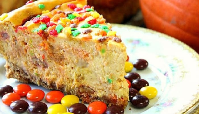 A super closeup photo of a slice of Reese's Pieces Pumpkin Cheesecake on a plate with Reese's pieces candy and fall sprinkles.