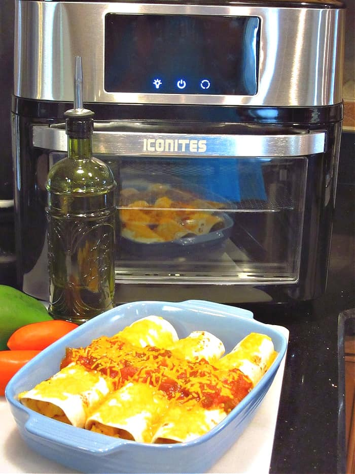 A vertical photo of a a blue casserole filled with air fryer breakfast burritos in the foreground and an air fryer in the background.