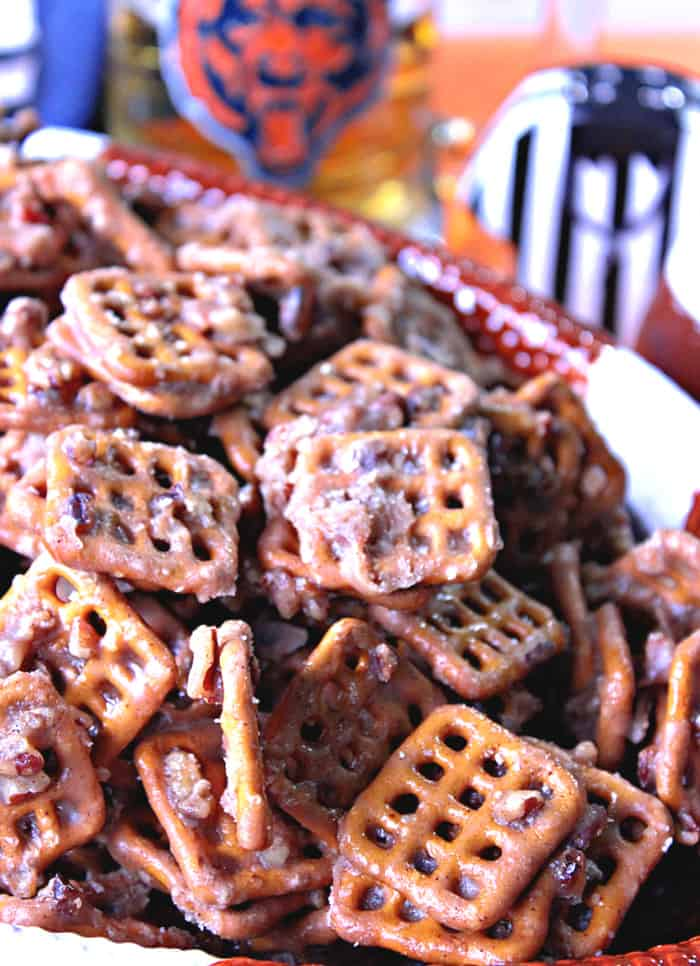 A closeup vertical photo a of bowl filled with Cinnamon Praline Pretzels and some football accessories in the background