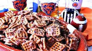 A football bowl filled with Cinnamon Praline Pretzels along with some football accessories in the background.
