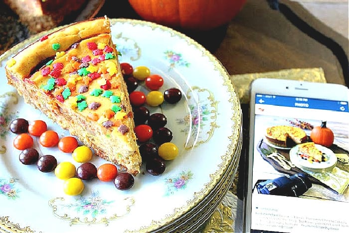 A slice of Reese's Pieces Pumpkin Cheesecake on a pretty plate with fall sprinkles and an iphone with a photo.