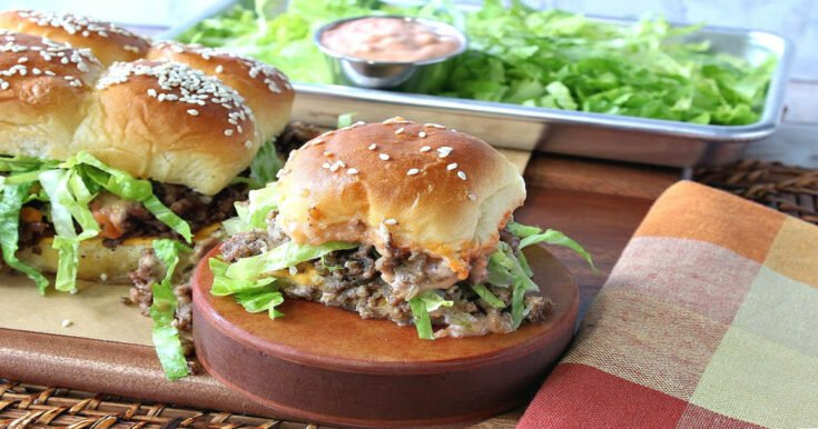 A big mac slider on a wooden pedestal with sliders in the background and a tray of lettuce and secret sauce