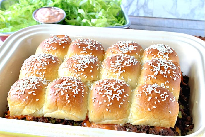 A baking dish filled with big mac sliders on sesame seed buns with lettuce and special sauce in the background.