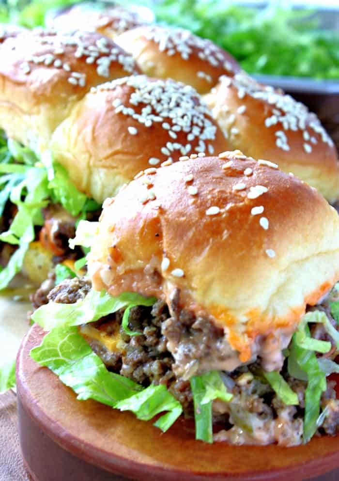 A vertical close up of a big mac slider with ground beef and lettuce on a sesame seed bun.
