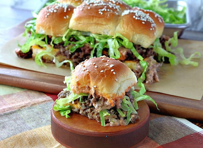 A big mac slider on a wooden pedestal with additional big mac sliders in the background.
