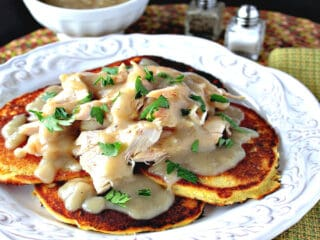 A pretty white plate filled with Chicken Chile Corn Cakes and covered with Buttery Maple Gravy and parsley as garnish