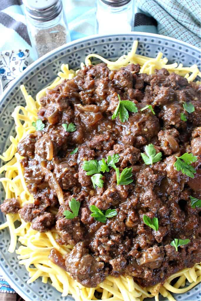 An overhead vertical closeup of a blue bowl filled with ground beef sauerbraten goulash served over noodles