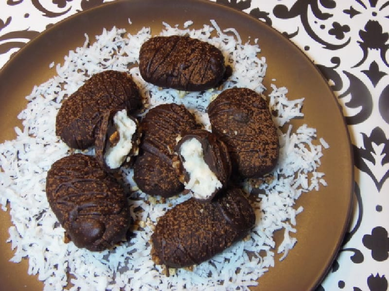 A brown plate filled with homemade almond joy candy on a bed of coconut.