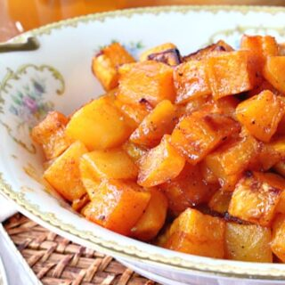 An offset horizontal photo of a pretty china bowl filled with honey roasted butternut squash