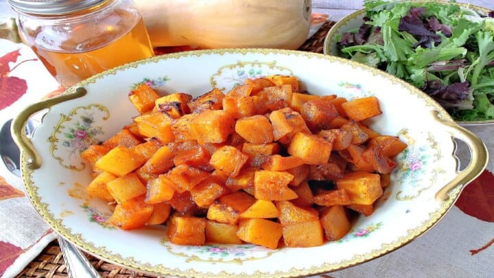 A pretty china bowl filled with honey roasted butternut squash along with a jar of honey in the background