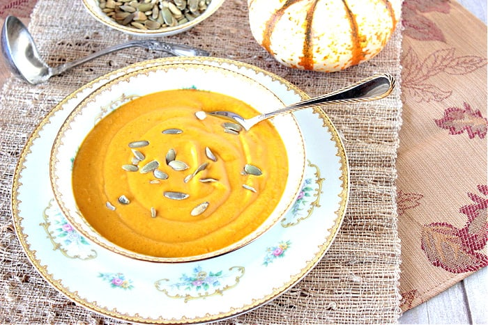 An offset photo of a bowl of Roasted Butternut Squash Soup on a textured placemat with a leaf napkin.