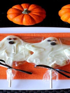 A lineup of white chocolate ghost pops on an orange napkin with mini pumpkins in the background