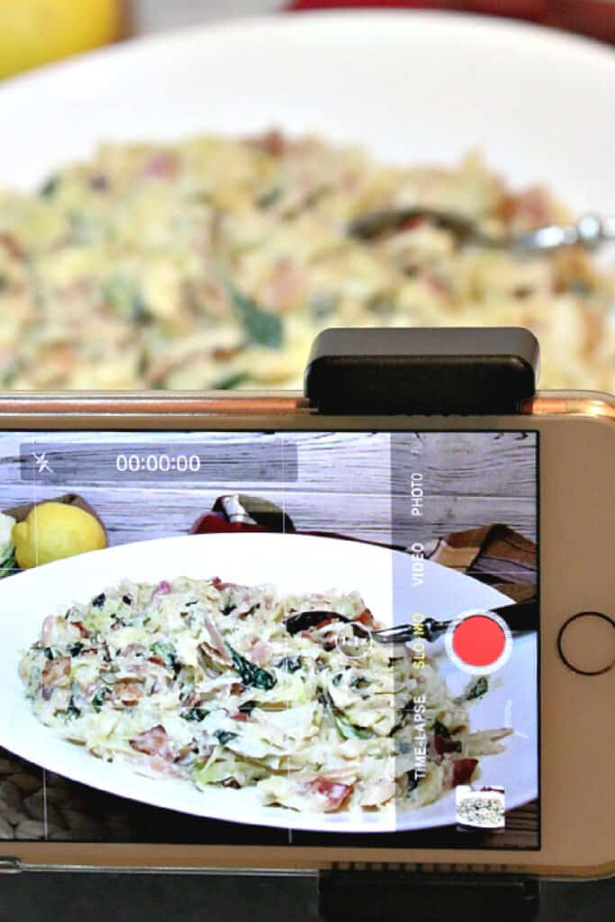 A vertical photo of a closeup of an iphone taking a video of Creamed Cabbage and Spinach recipe