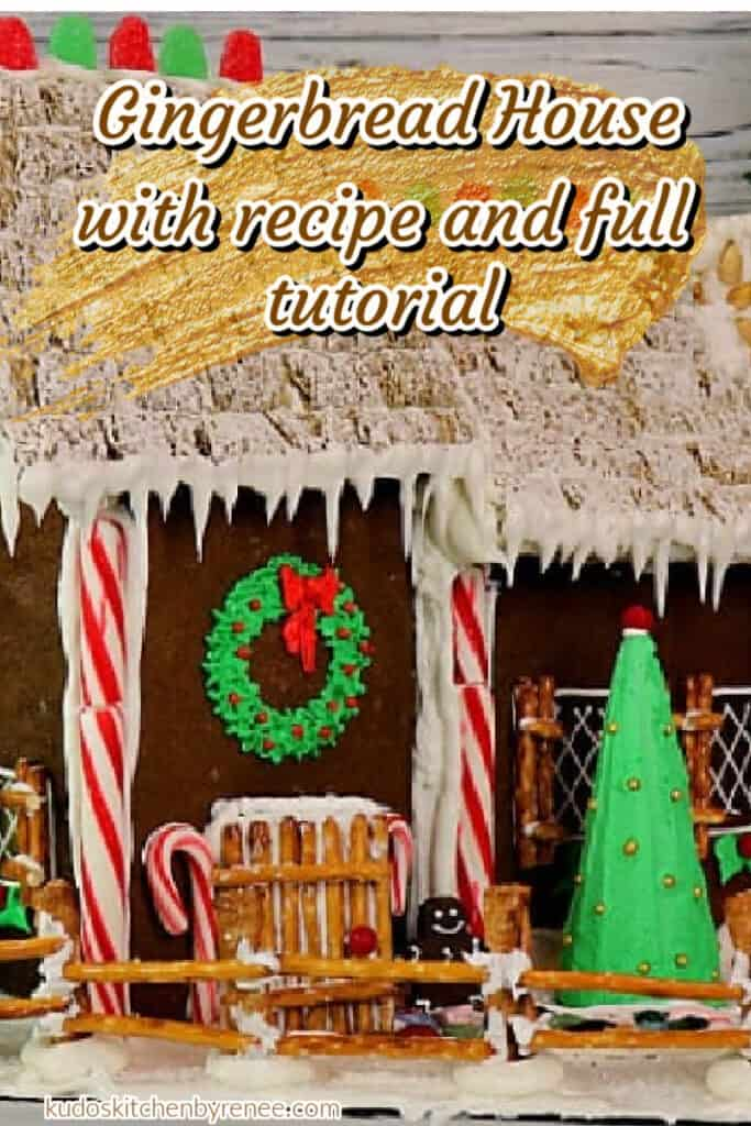 A closeup vertical image of a Gingerbread House Recipe with pretzel sticks, peppermint sticks, royal icing, and a green wreath above the door with a title text overlay graphic.