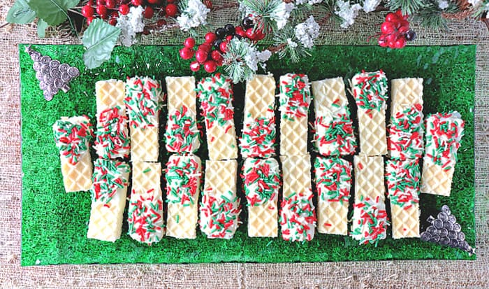 A direct overhead photo of a green glass rectangle plate filled with No-Bake Peppermint Buttercream Wafer Cookies with snow covered greens and berries in the background.
