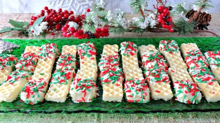 A bunch of Peppermint Buttercream Wafer Cookies on a green glass plate with holiday sprinkles.