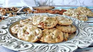 A pretty scalloped plate holding a pile of Take 5 Cookies with a butter dish and pretzels in the background.