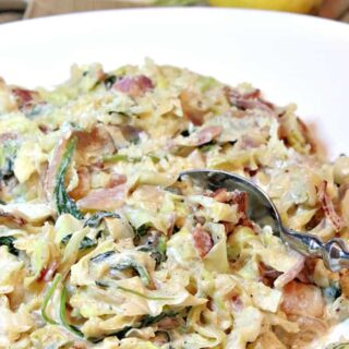 A closeup photo of Creamed Cabbage and Spinach in a white bowl with a serving spoon