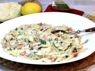 An oblong white bowl filled with Creamed Cabbage and Spinach with a serving spoon in the center.