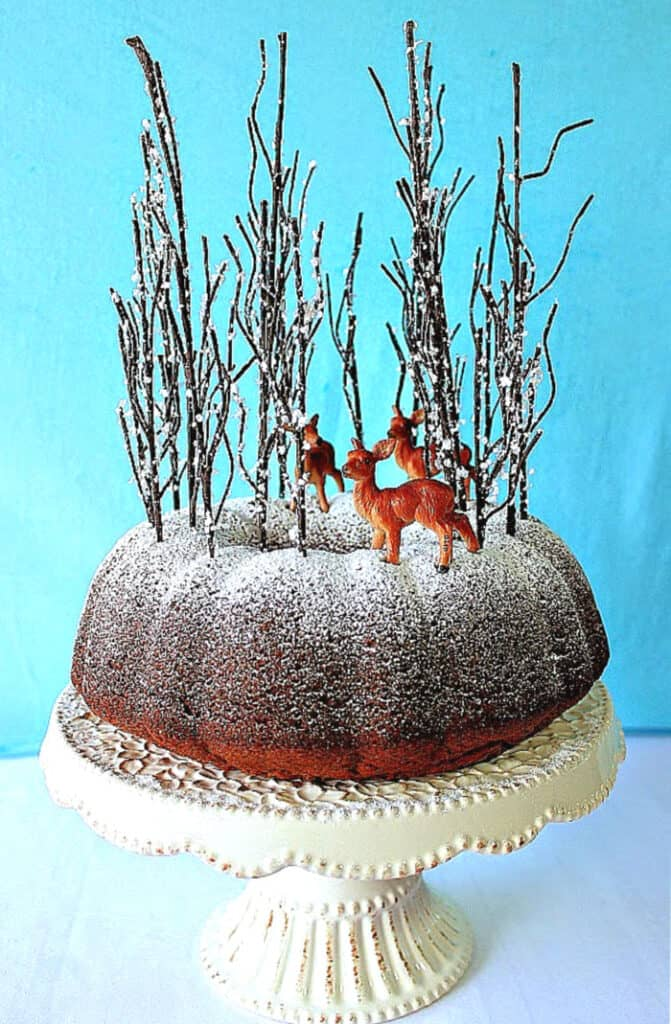 A Gingerbread Forest Cake with confectioners sugar dusting and tall trees with deer.