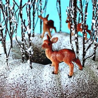 A closeup of a gingerbread forest cake with faux trees and deer