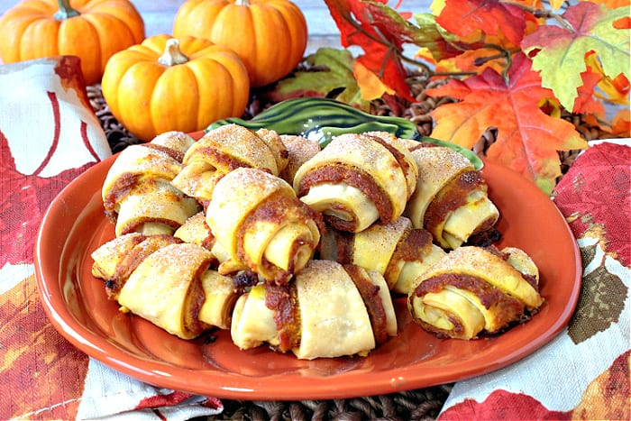 A centered photo of a pumpkin plate filled with Pumpkin Pie Bites with real mini pumpkins in the background along with autumn leaves.