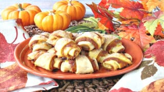 A bunch of Pumpkin Pie Bites on a small pumpkin plate with real mini pumpkins in the background and fall leaves.